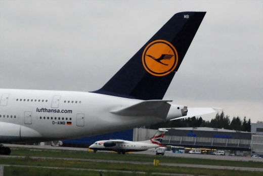 Lufthansa A380 at Helsinki, a small plane taxiing next to it